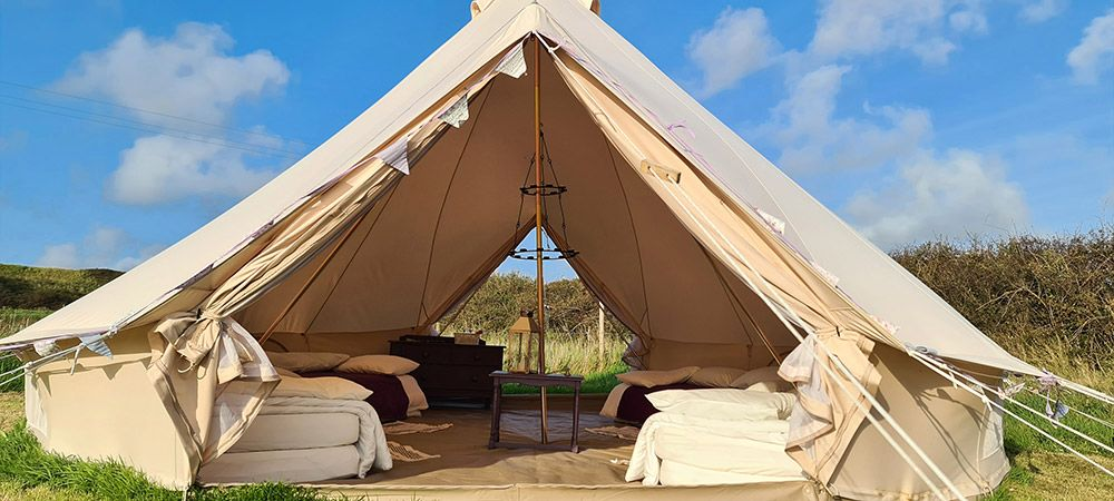 Bell-tent-glamping-at-Warren-Farm-Wales---looking-into-a-bell-tent-on-a-sun