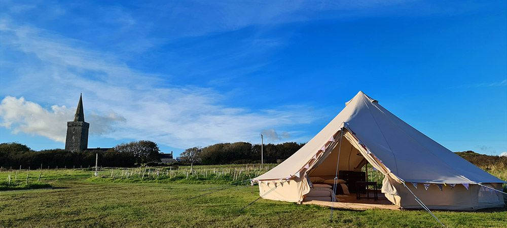 Bell-tent-glamping-at-Warren-Farm-Wales---bell-tent-and-church-with-clear-b