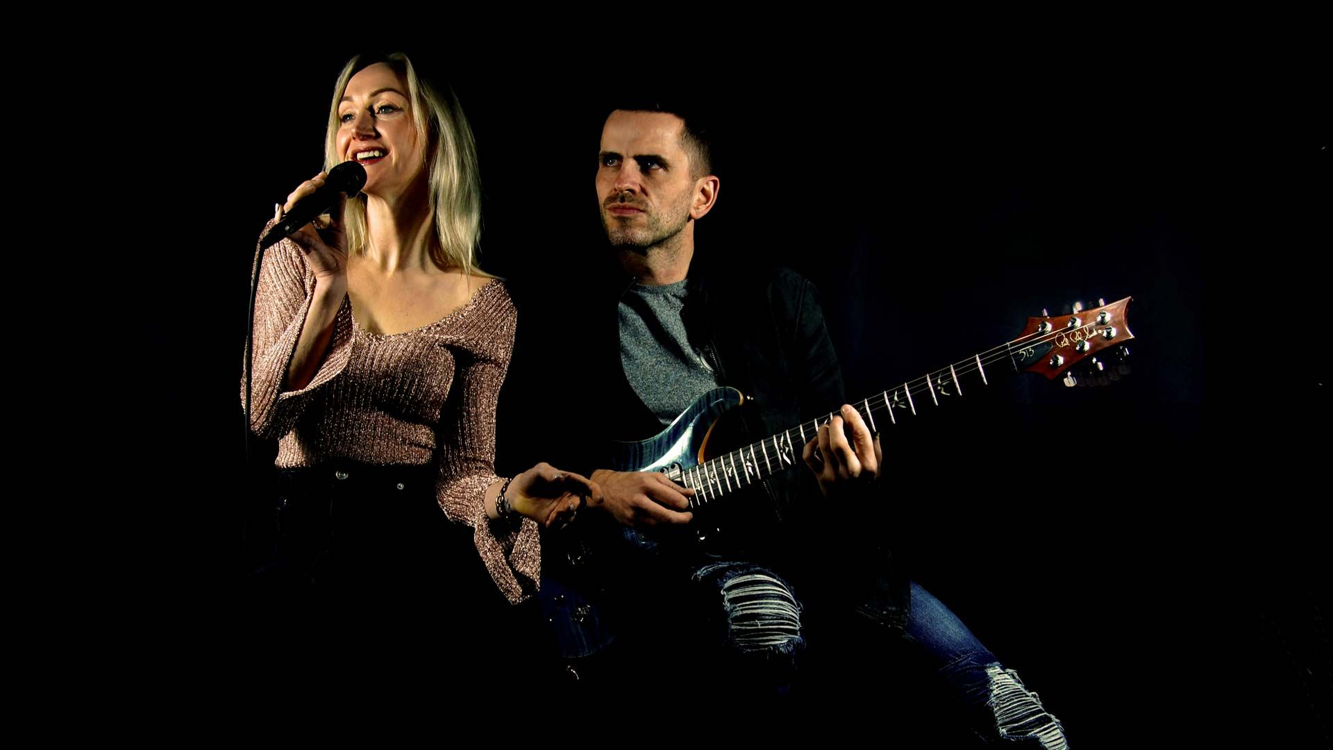Glow Band Michelle and James on Black with guitar and mic
