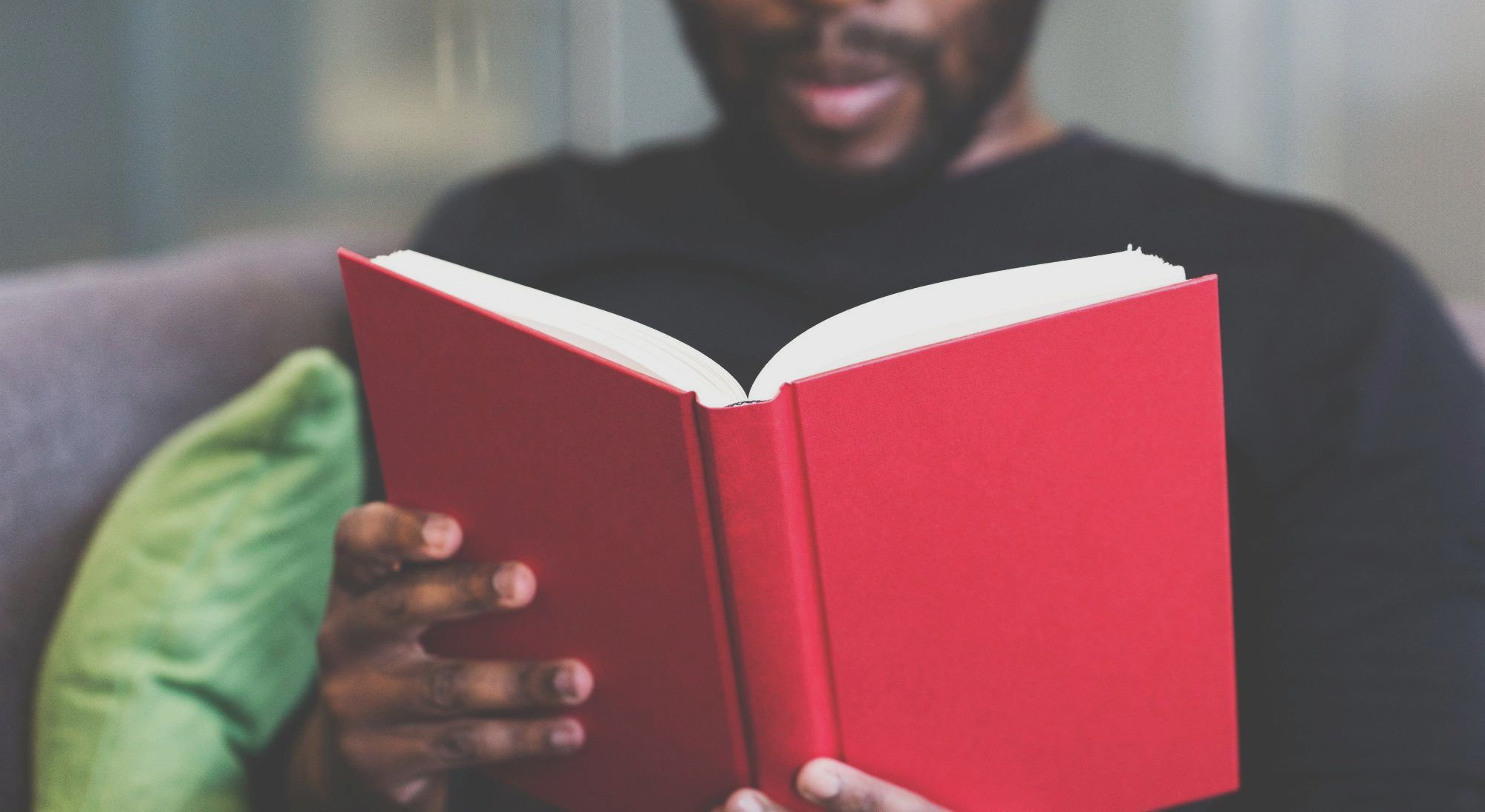 What? - A man, out of focus,  reading a red book