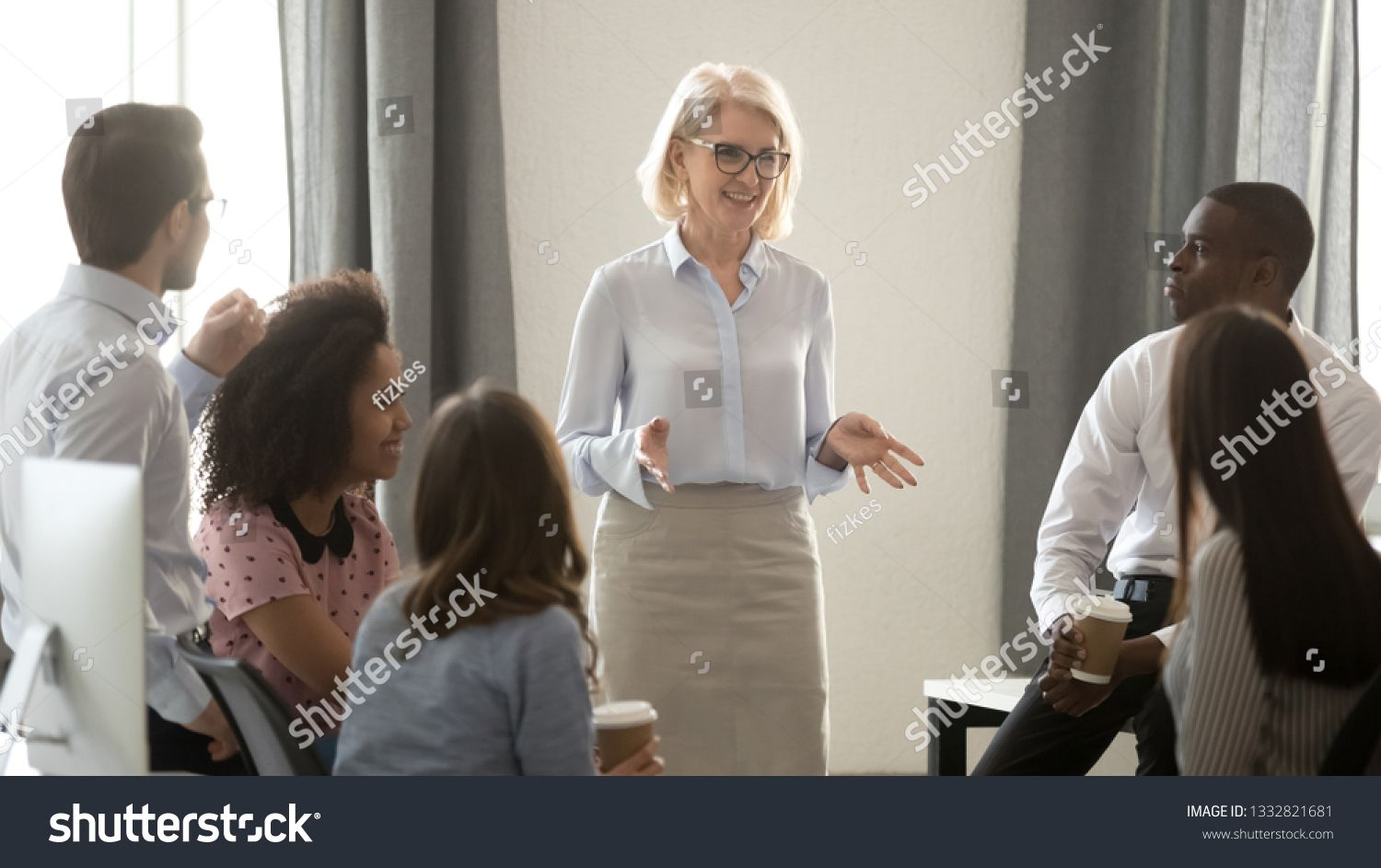 stock-photo-old-woman-mentor-coach-speaker-training-multicultural-interns-g