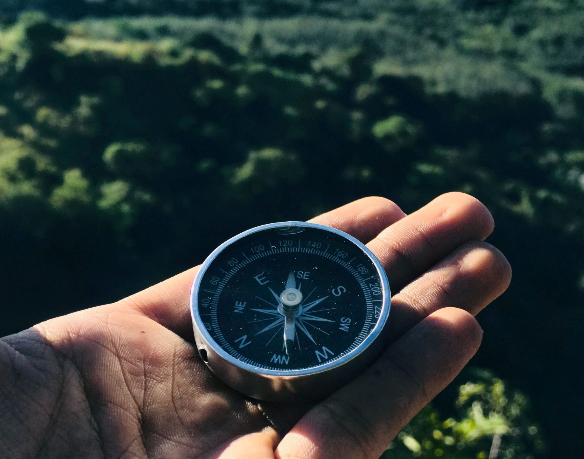 Close up of a man's hand holding a compass