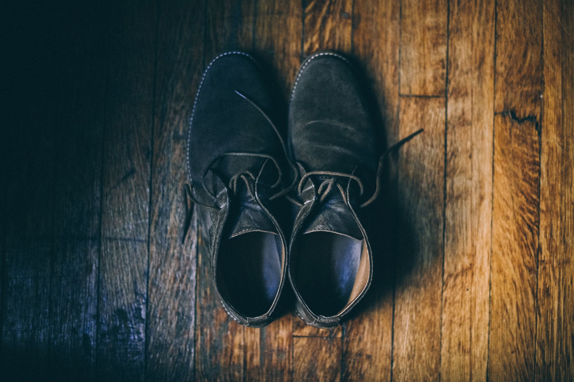 Aerial shot of a pair of shoes on a wooden floor