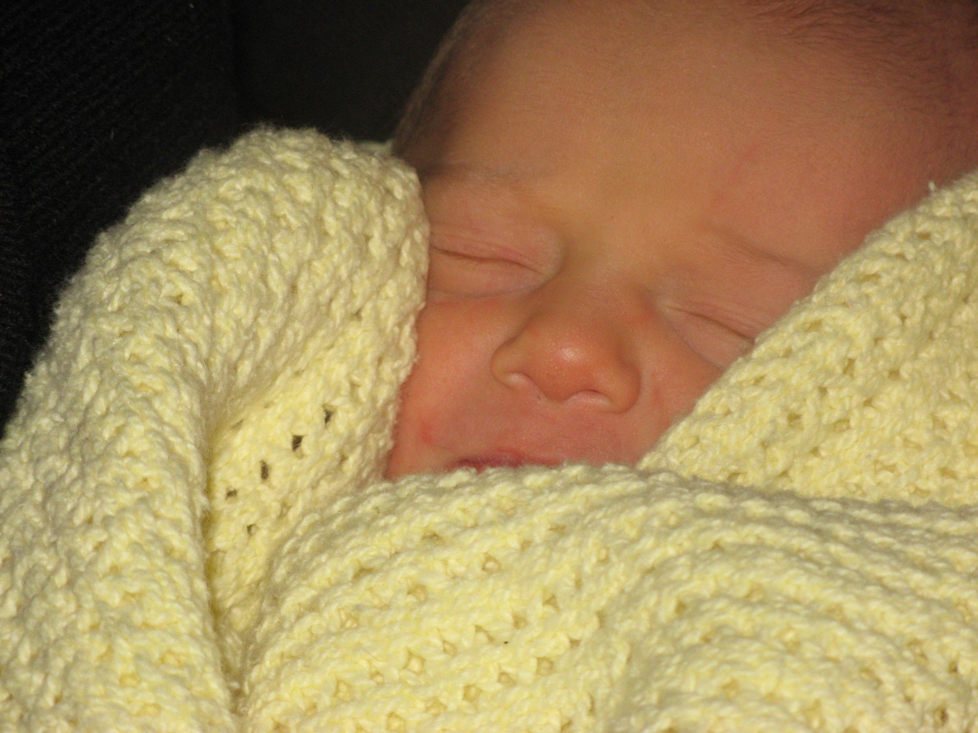 A close up of a sleeping newborn baby's face. They are wrapped in a yellow blanket.