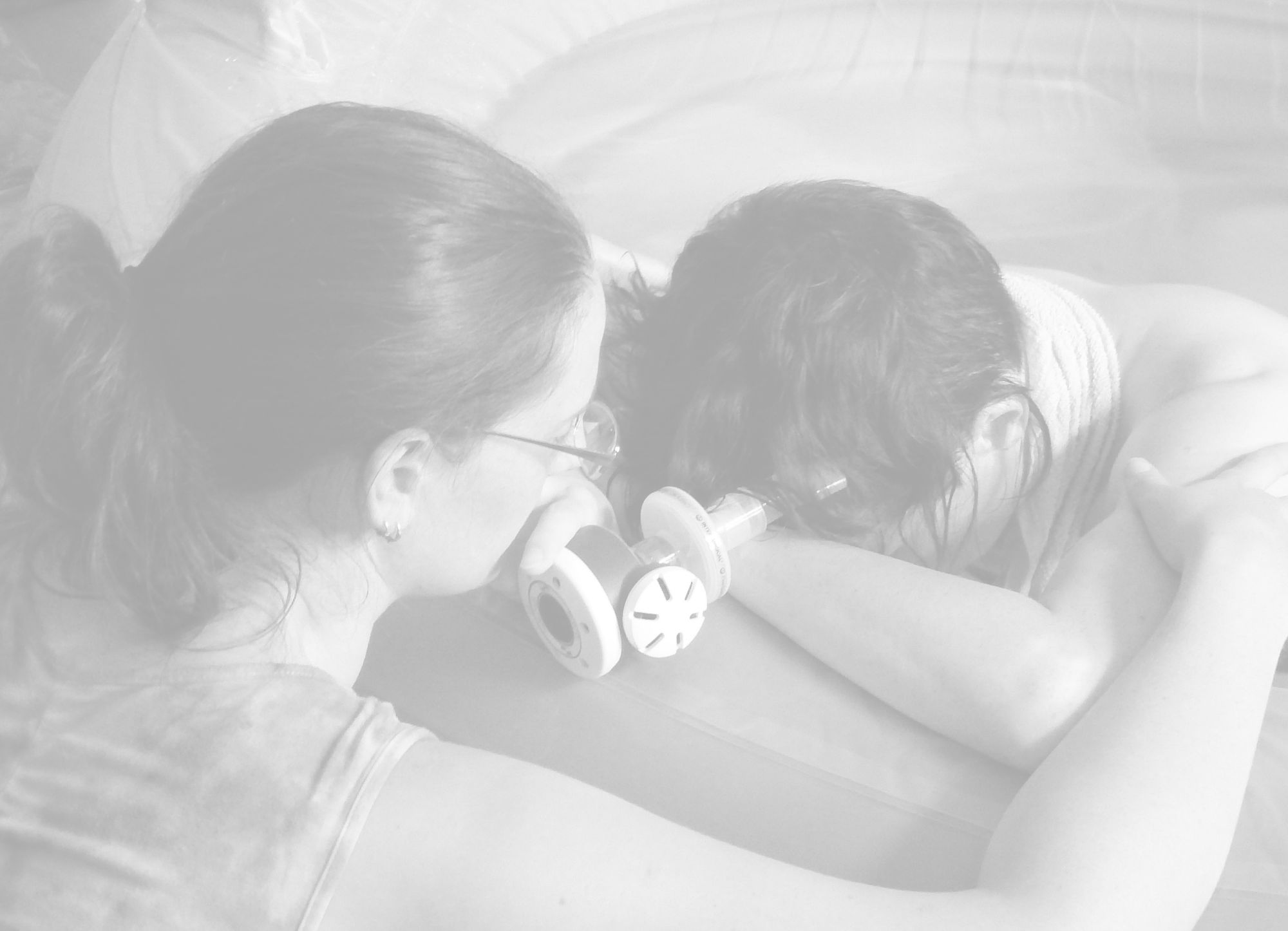 Black and white image of Caz comforting a labouring woman in a birth pool