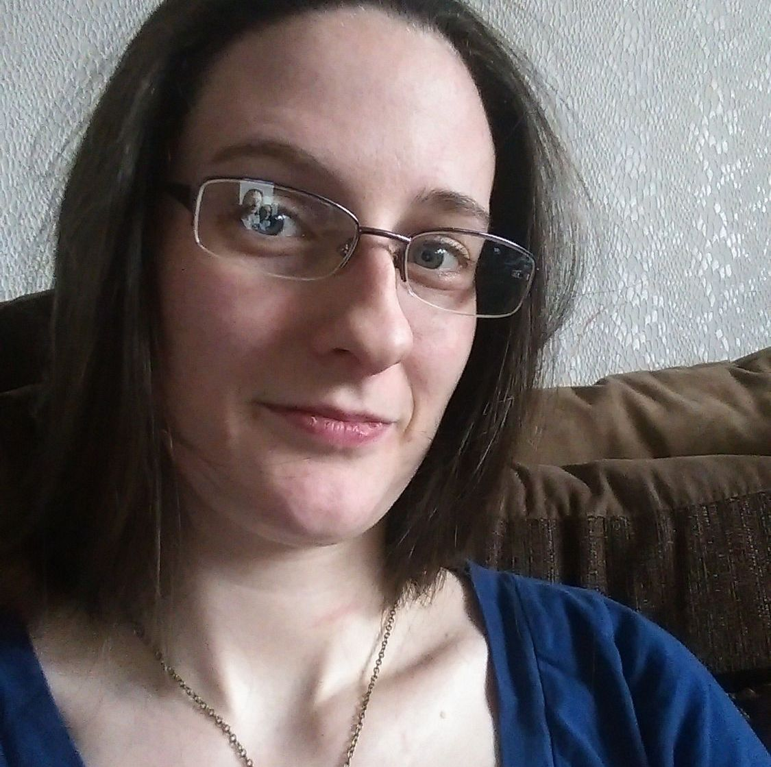 A headshot of Caz. Her hair is loose and dark brown. She wears glasses and a medium blue top.