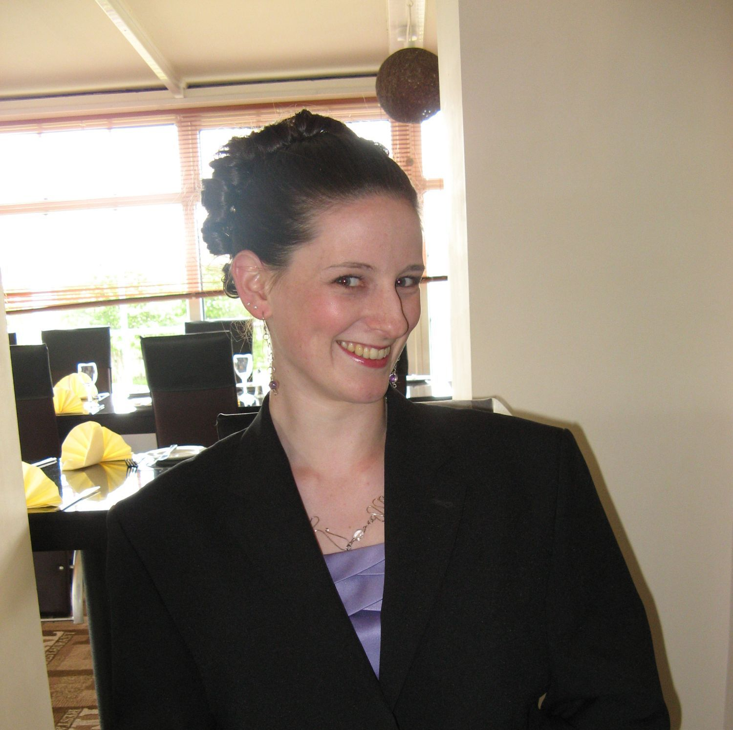 An image of Caz dressed up for a wedding. She is wearing a suit jacket over a lilac dress, and her hair is done up in curls around the crown of her head.