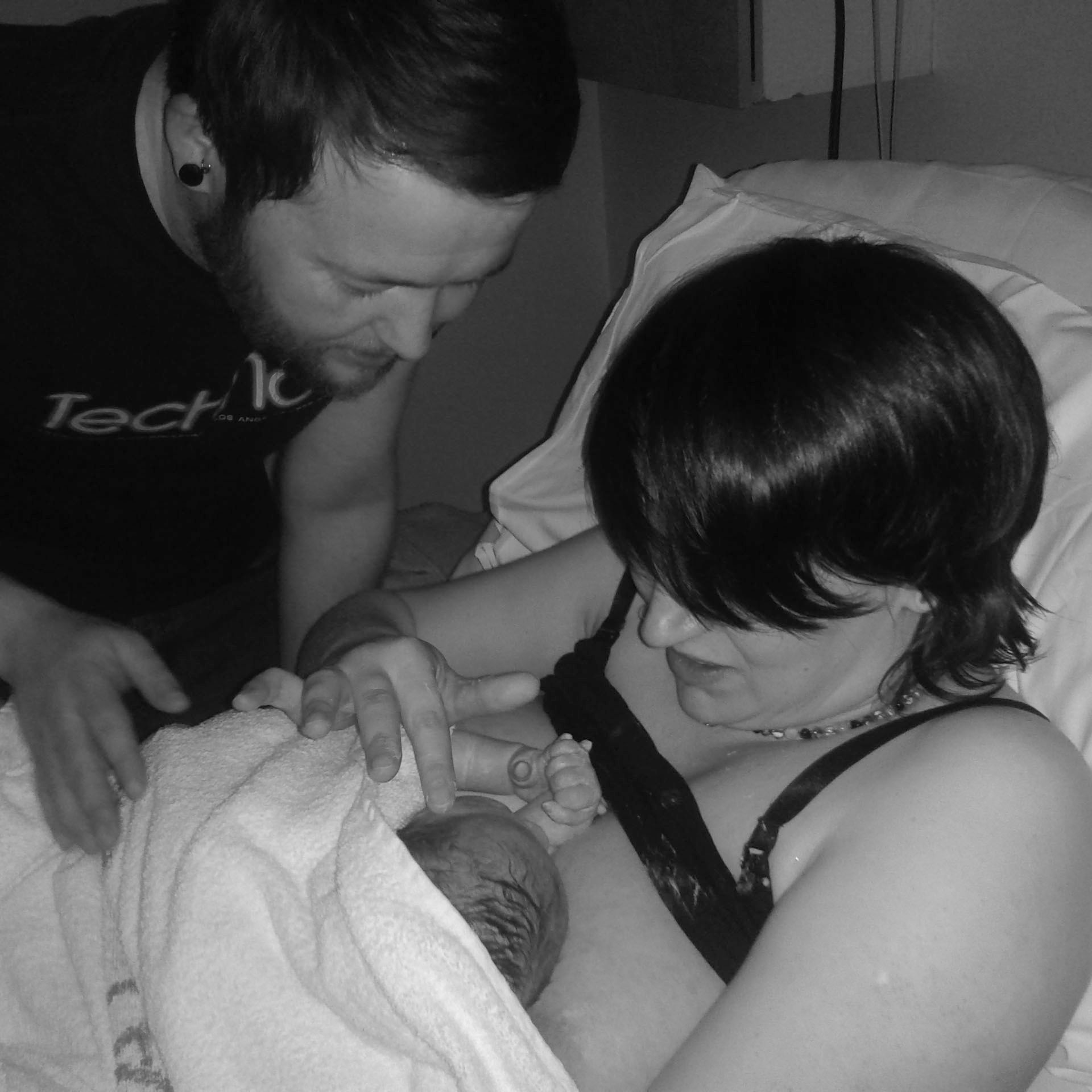 A woman holds her newborn baby to her chest, and touches her face with a finger. Her partner looks down on them both.