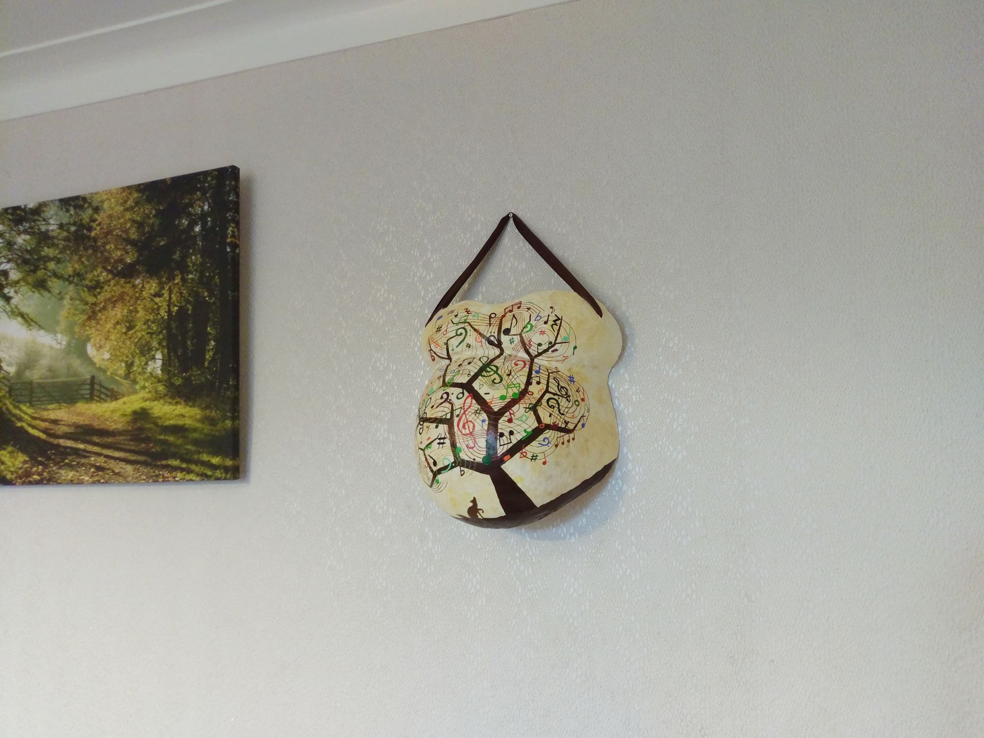 Image of a painted belly cast hanging on a wall.