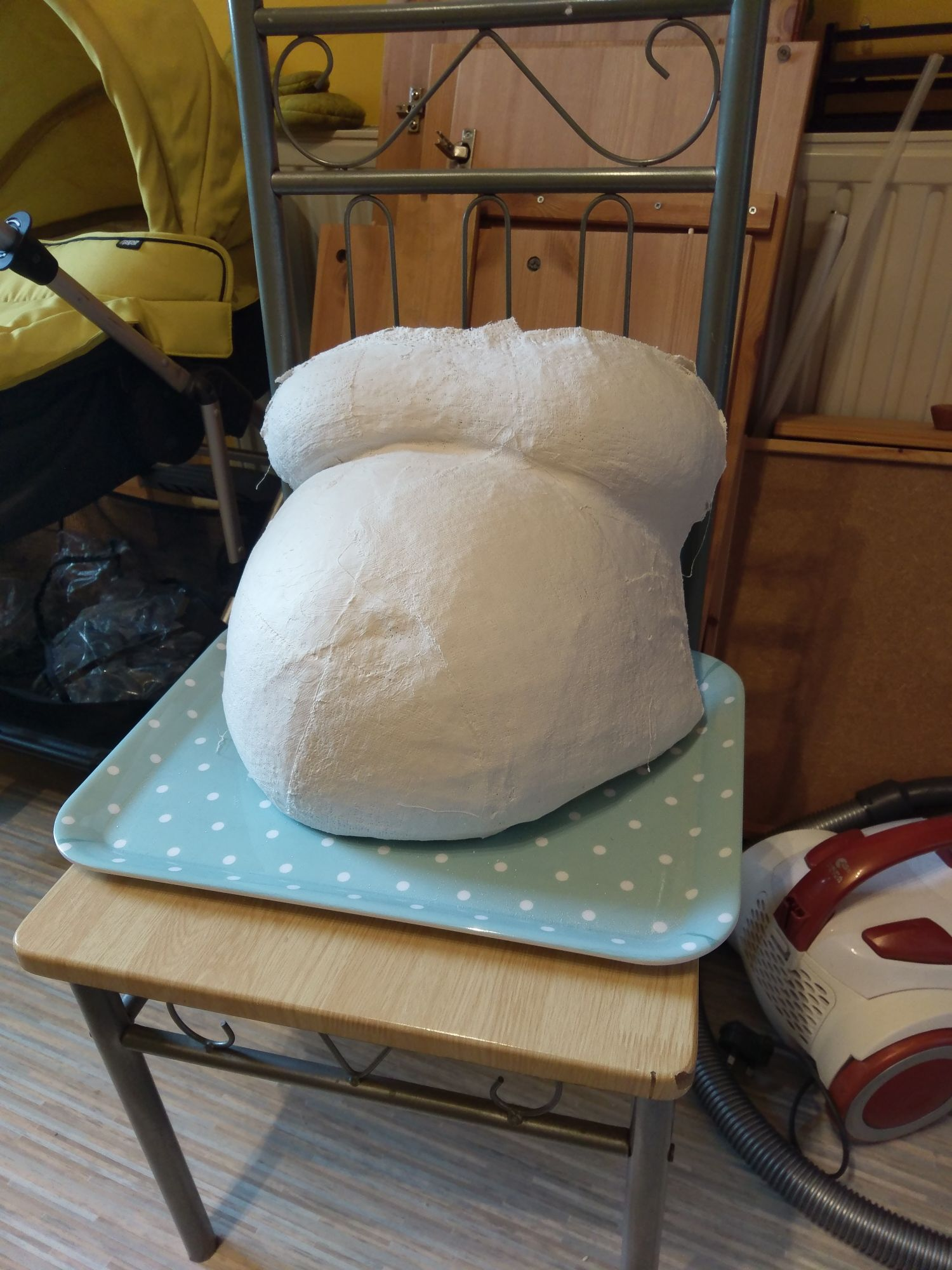 A belly cast that is unfinished. It has rough edges and only a couple of layers of plaster.