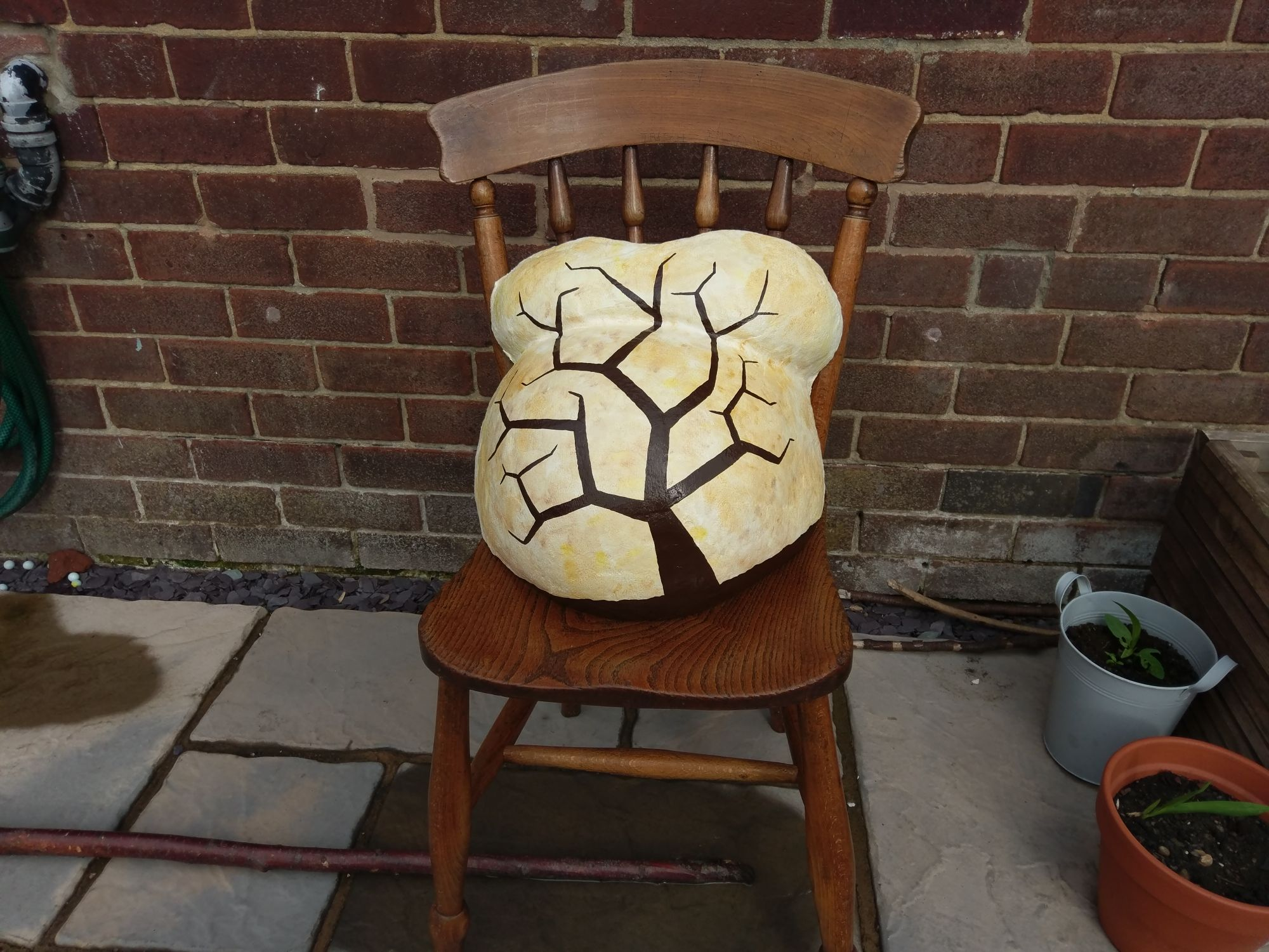 The cast on a chair with a tree trunk and branches painted on it.
