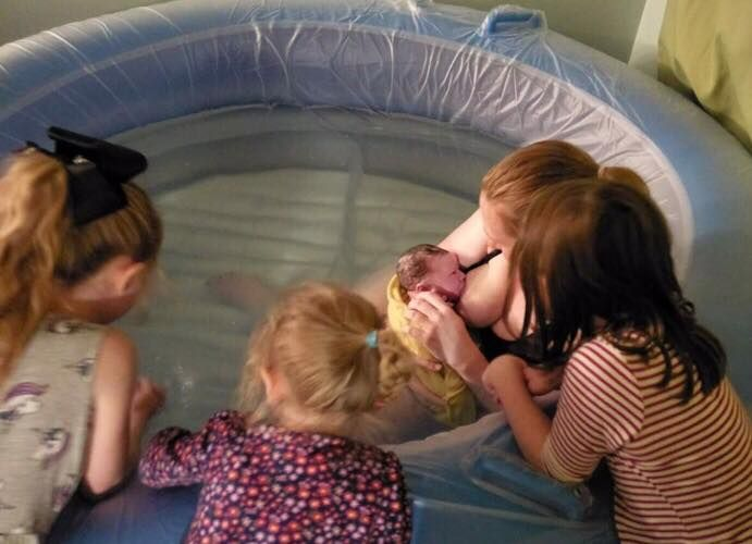 Image of a woman holding a newborn baby in a pool, while her other children look on.