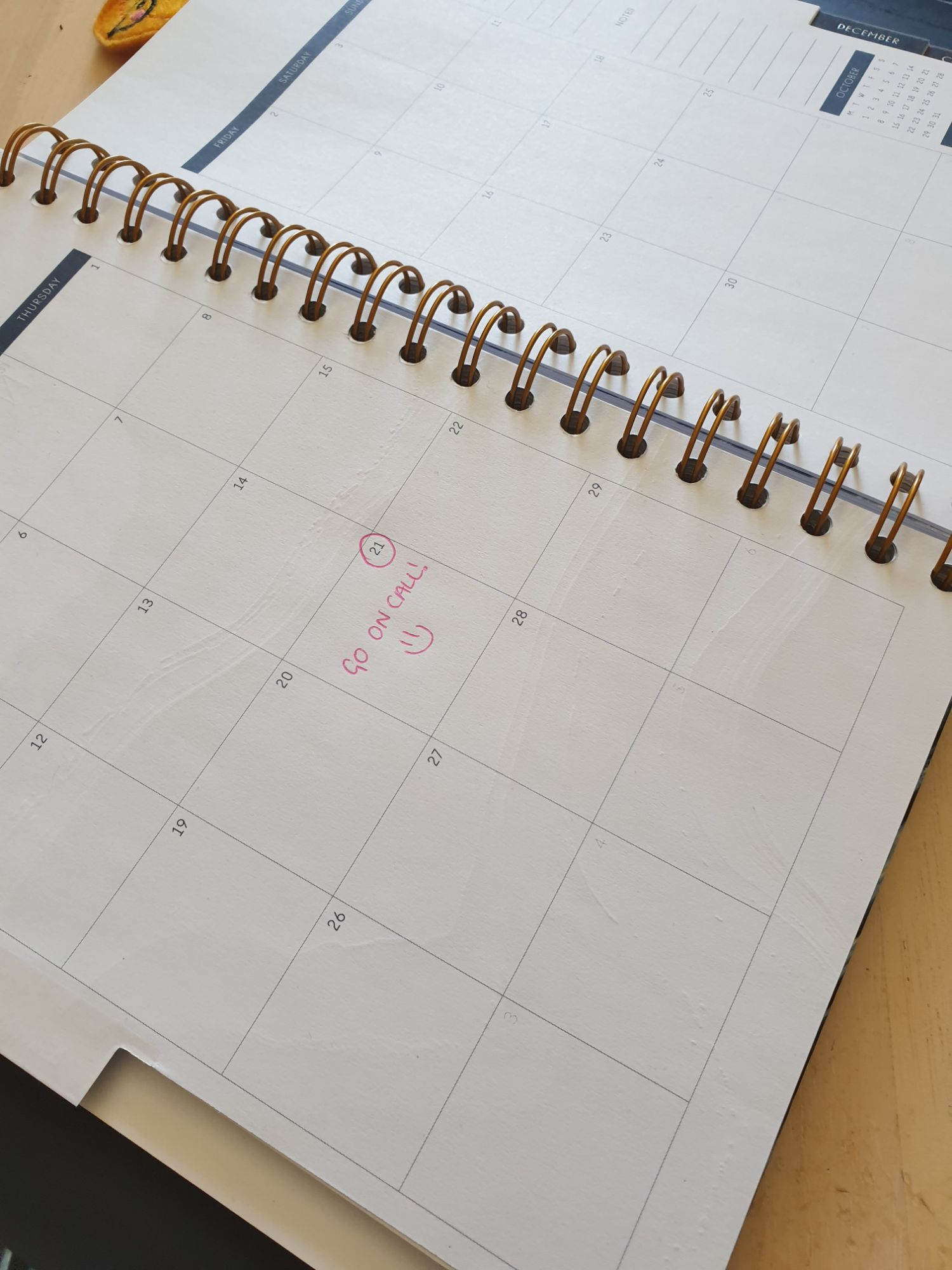 "A diary is open with a month viewable across a two page spread. One date is circled with the words ""Go on call!"" and a smiley face."