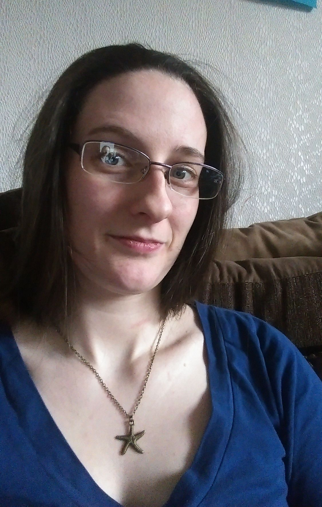 An image of Caz sitting on a sofa. She wears glasses. Her hair is loose and she is wearing a blue top and a necklace with a starfish on it.