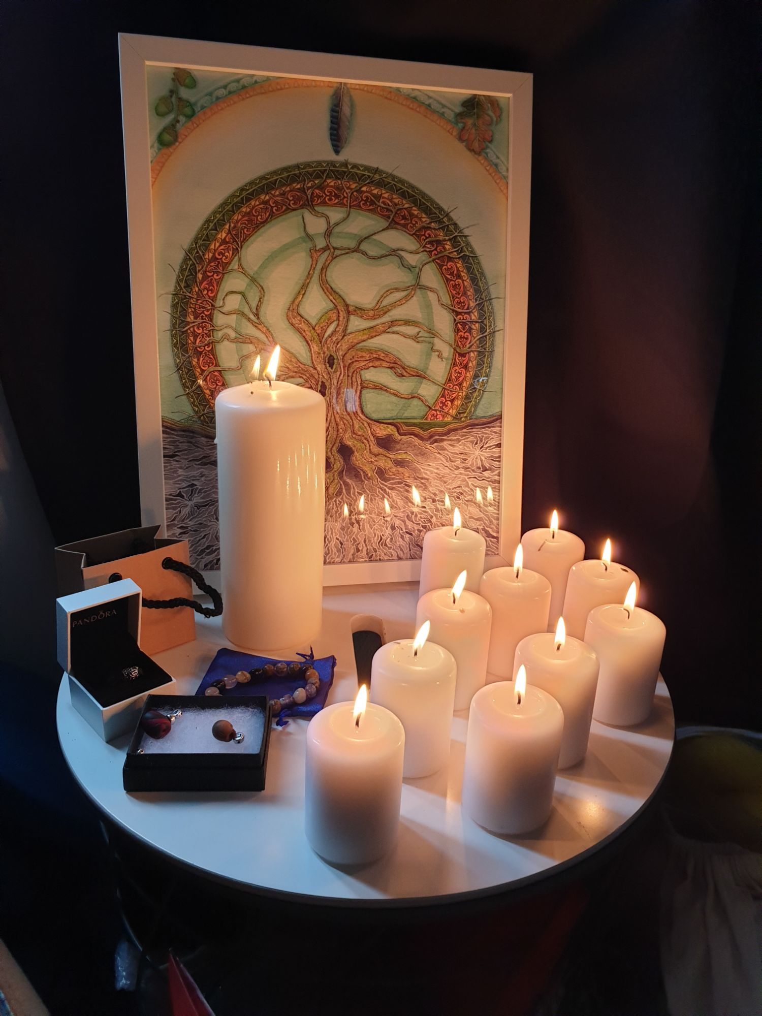 Image of a focus table at a Mother Blessing. A large framed print of a tree of life stands at the back, with a large pillar candle and several smaller candles standing lit in front of it, along with a collection of beads gifted to the mother.