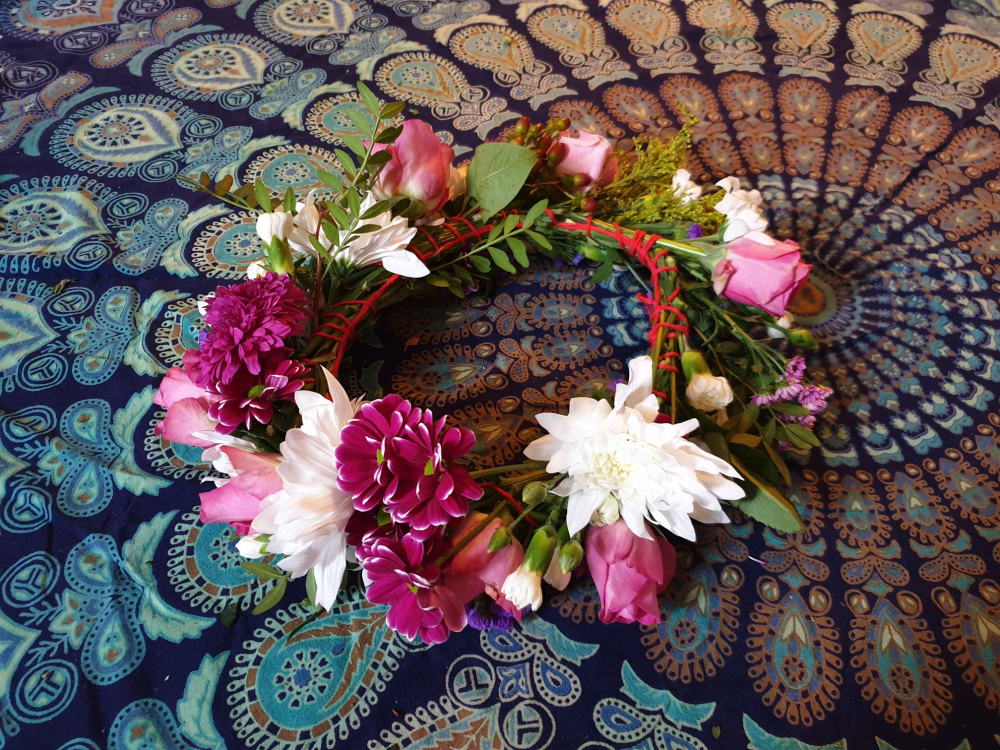 A flower crown made from fresh flowers. The flowers are pink, purple and white and woven together with yarn.