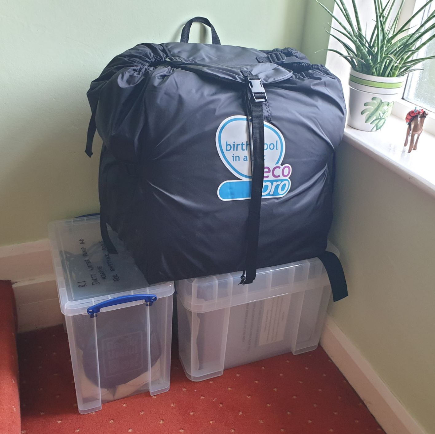 2 lidded plastic boxes on the floor, with a birth pool in a storage bag on top of them.