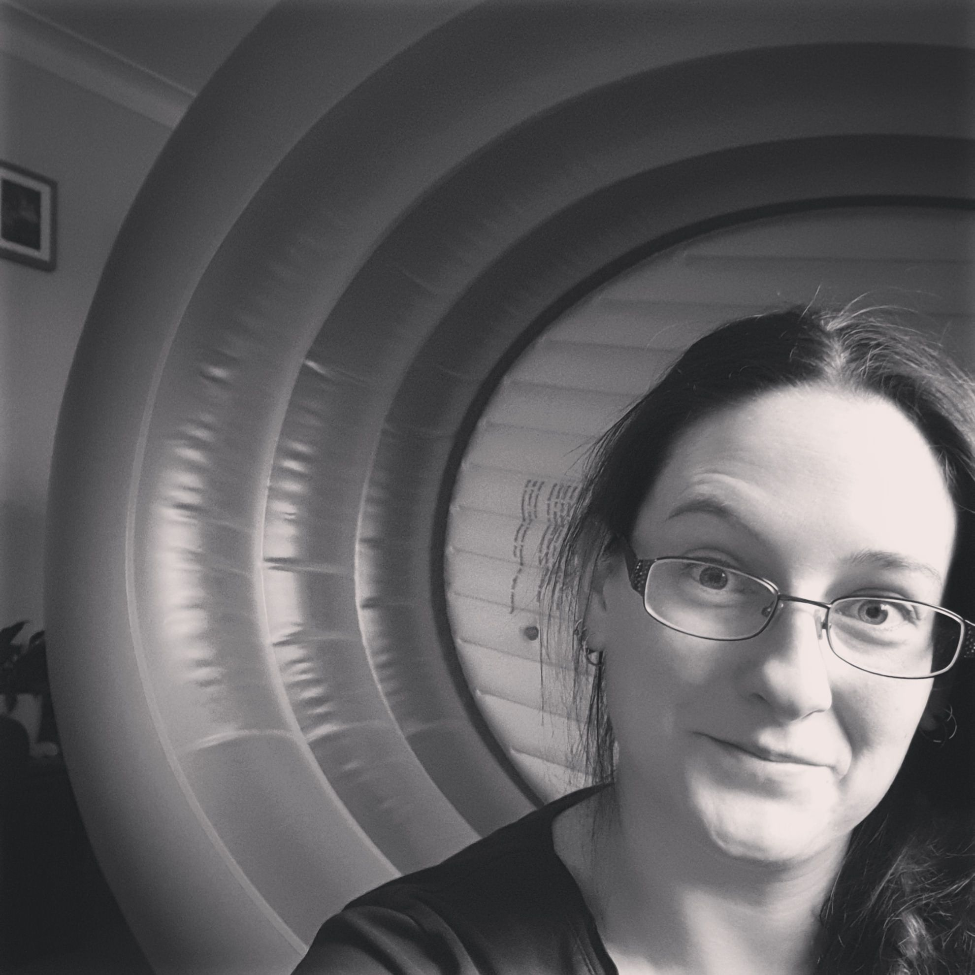 A black and white image of Caz looking into the camera. Her hair is plaited forward over her shoulder. Behind her is an empty birth pool on its side.