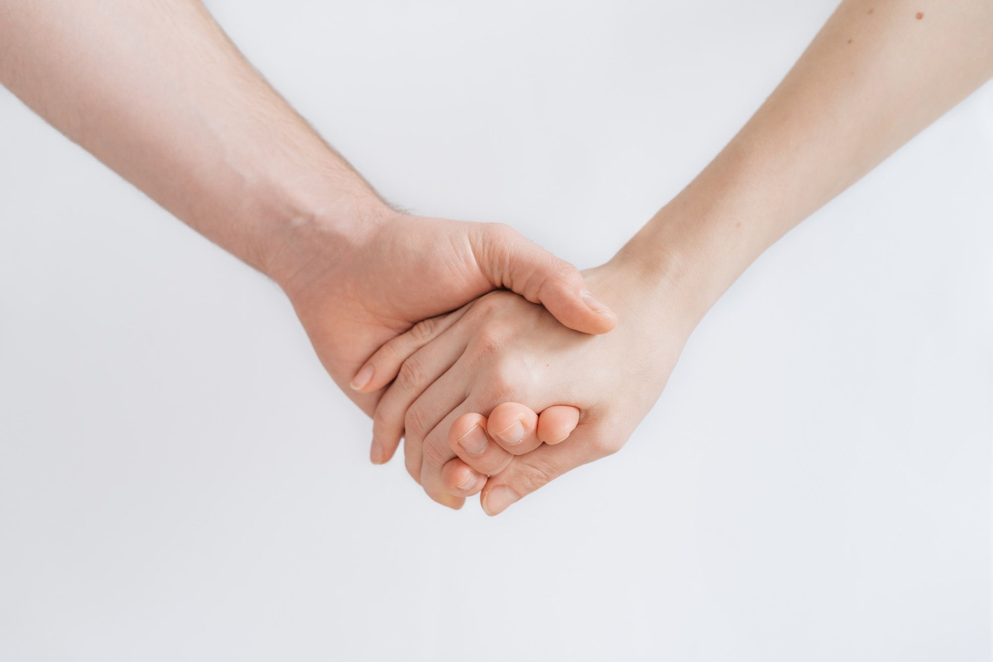 Two hands linked together, against a white background.