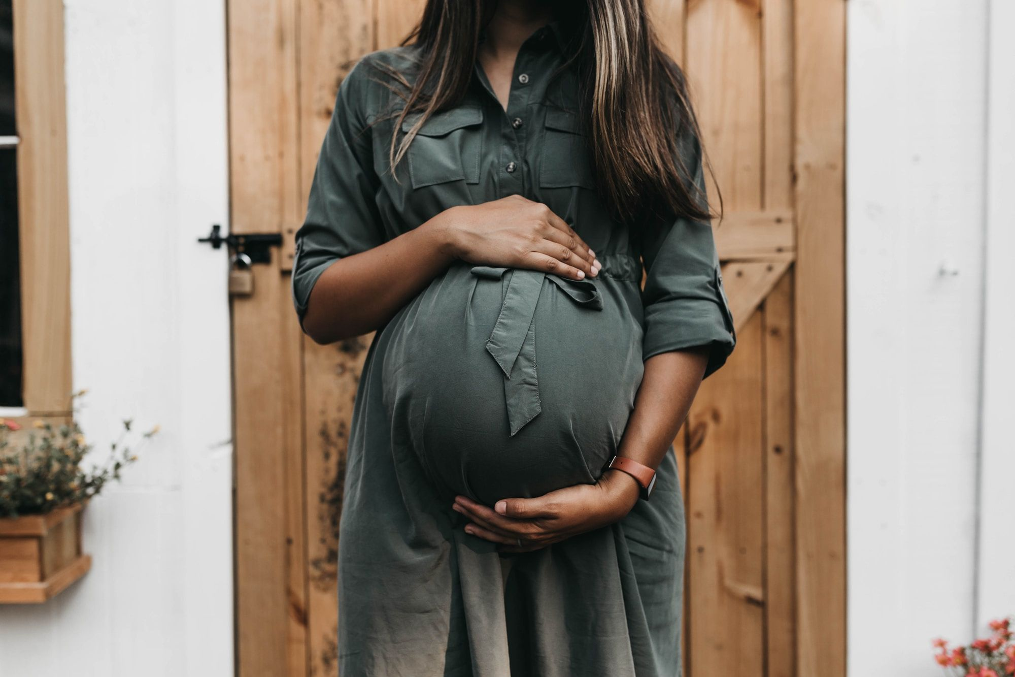 Image of a woman standing in front of a wooden door, her arms cradling her pregnant belly.