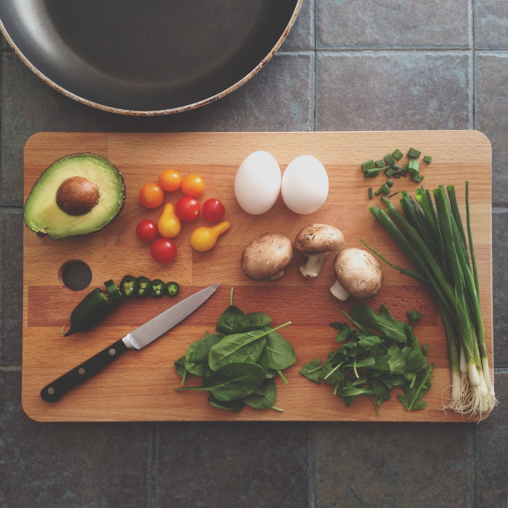 Flatlay image of various meal ingredients on a chopping board. A frying pan is nearby.