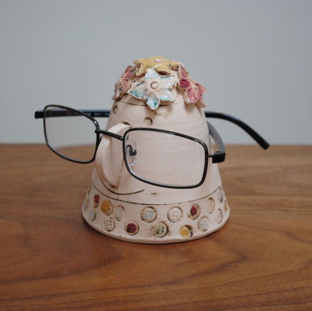 Handmade ceramic glasses stand from a white clay, decorated with red, pink,