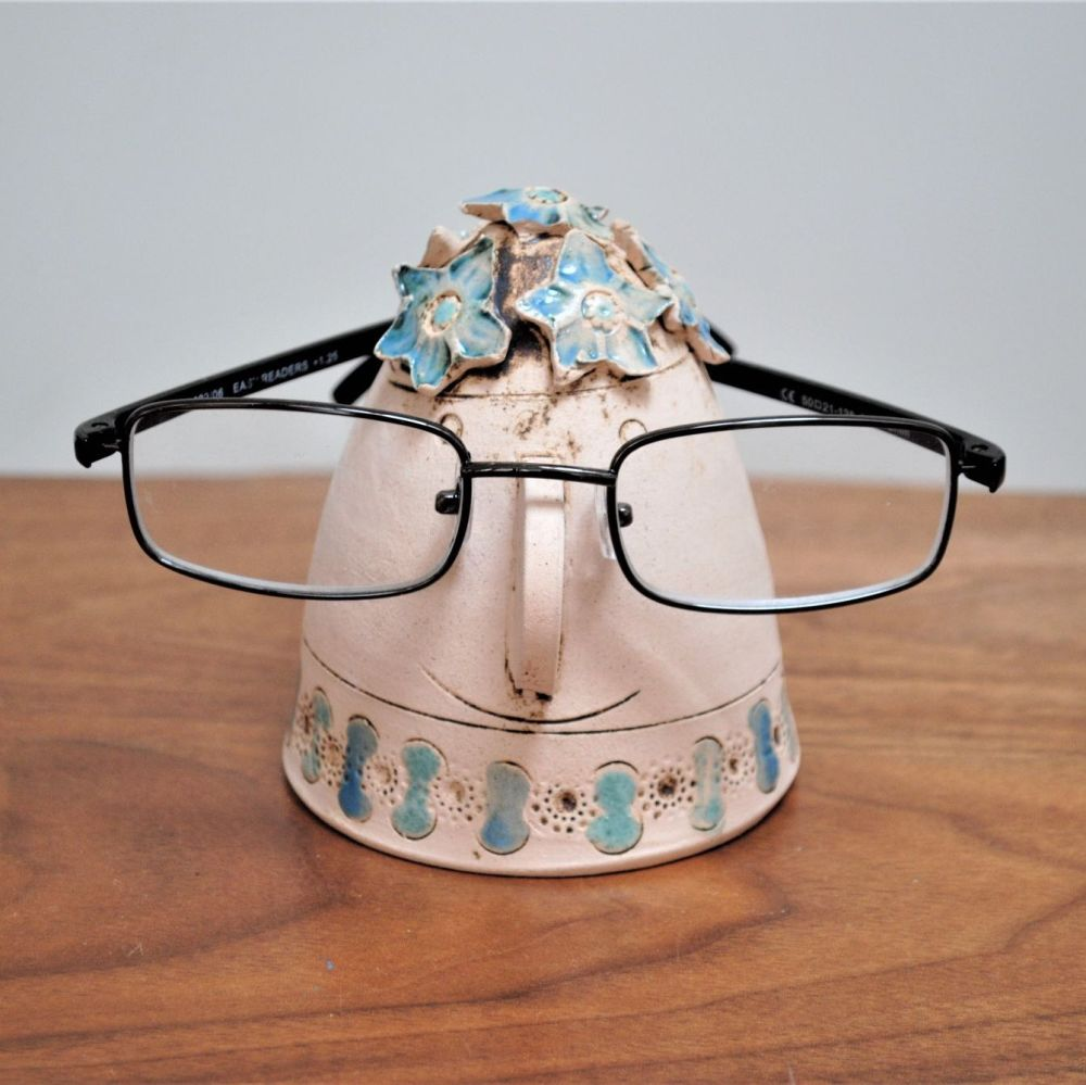 Handmade ceramic glasses stand from a white clay, decorated with blue flowe