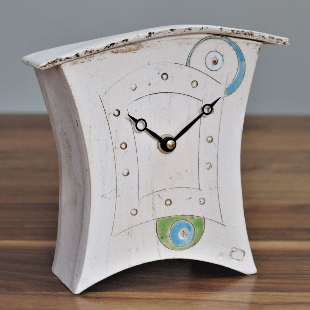 Handmade ceramic clock with green and blue circles and dots.