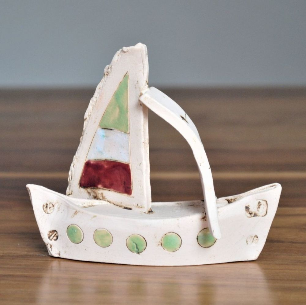 Small sailing boat made from white clay and decorated with green, red and w