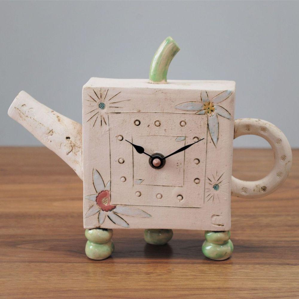 Handmade ceramic mantel teapot clock with feet and flower design.