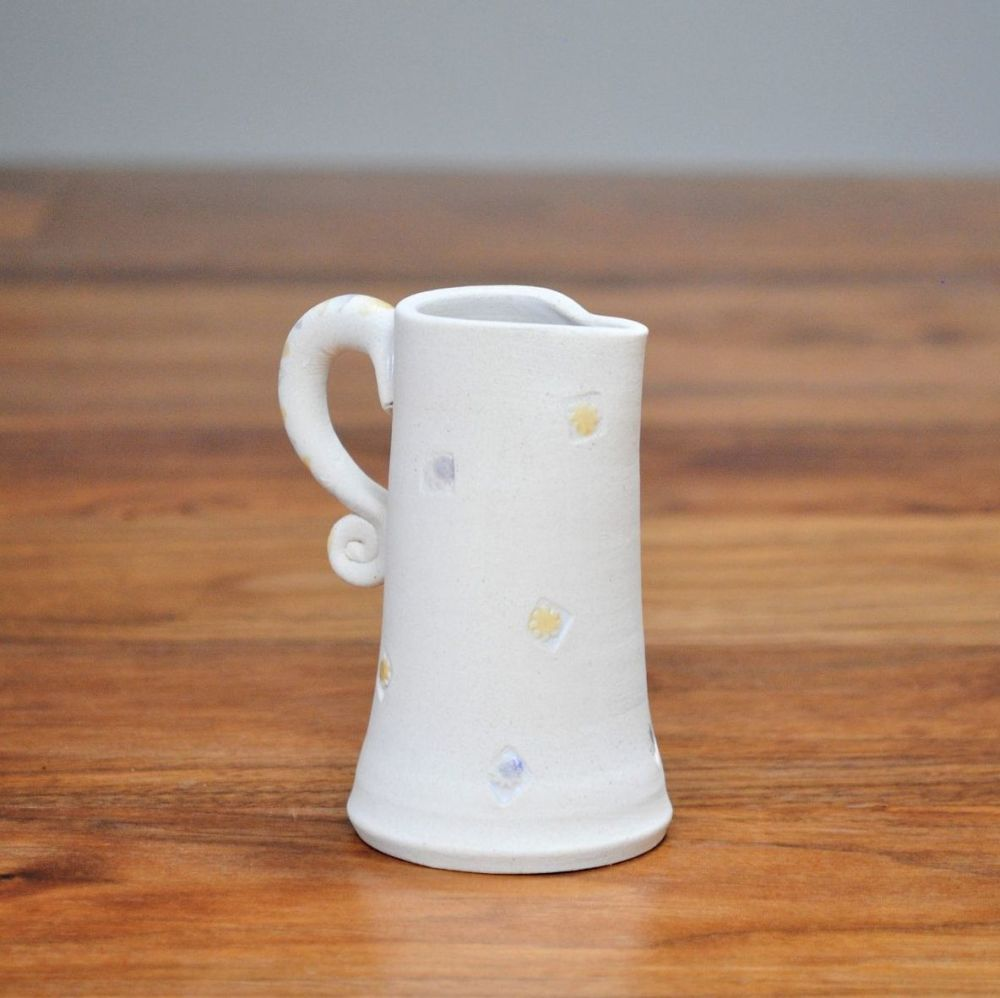 Jug / vase thrown on pottery wheel from white stoneware with yellow & purpl