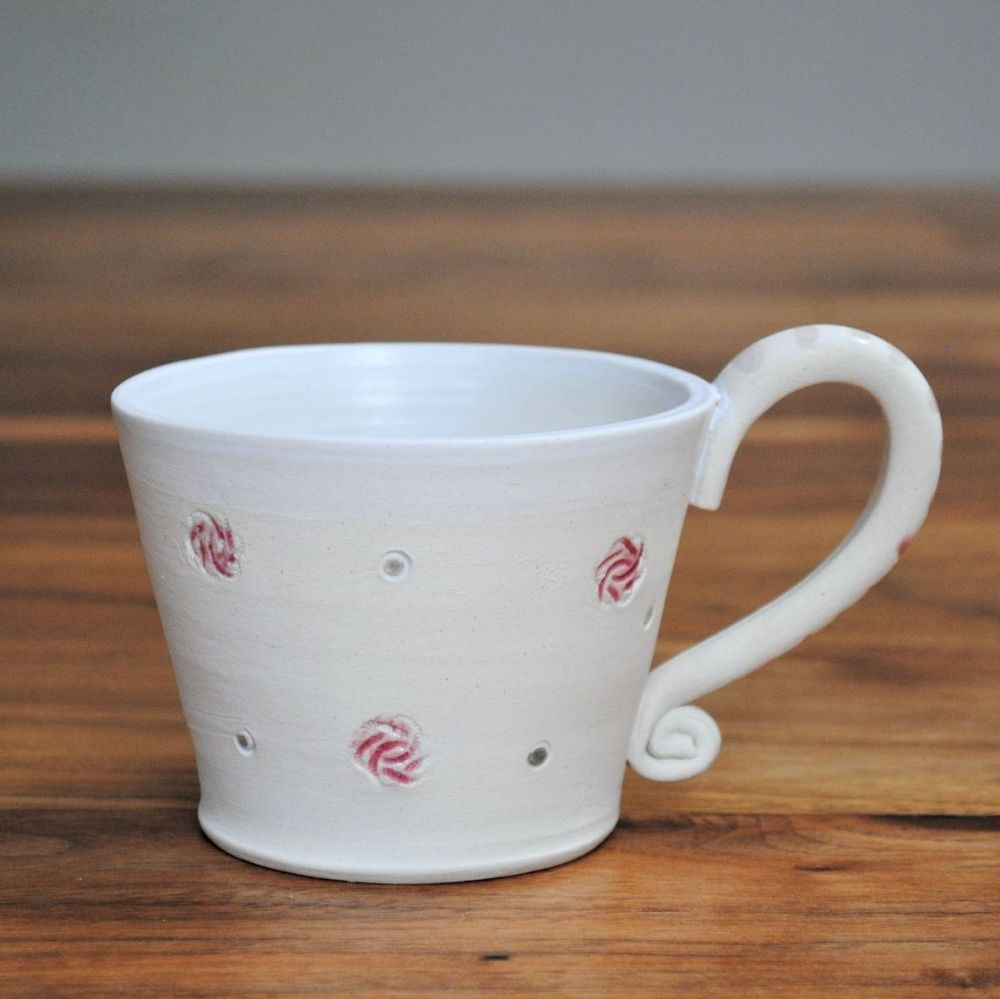 Mug thrown on the pottery wheel from white clay with pink details. Microwav