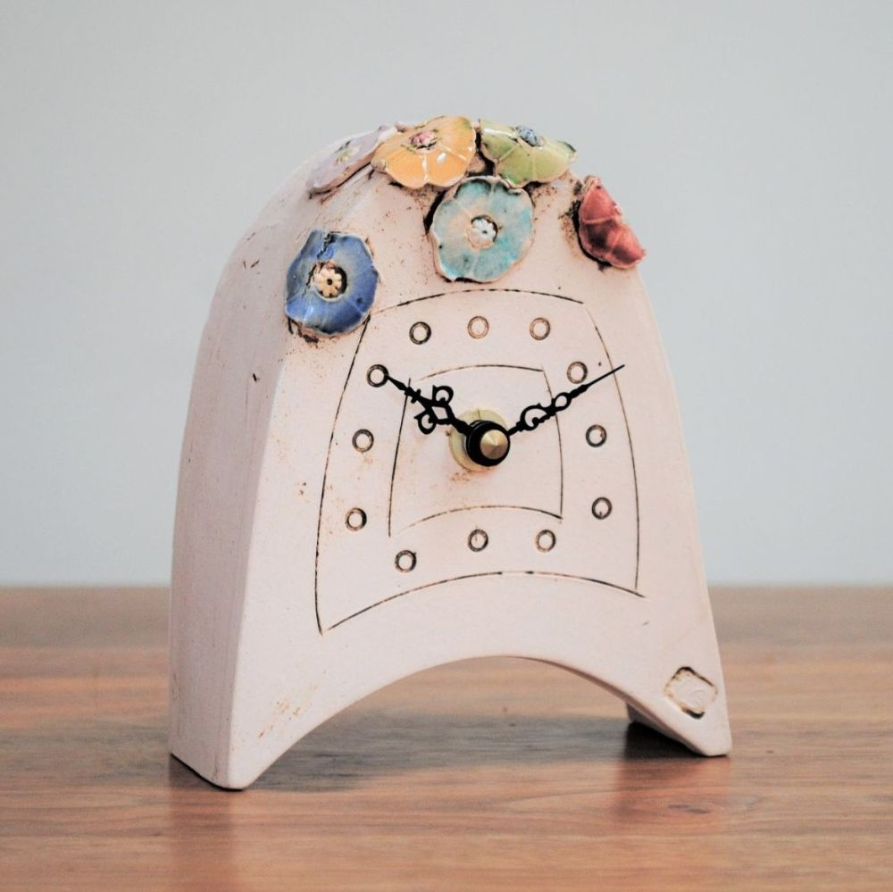 Small ceramic handmade clock from a white clay and decorated with bright co