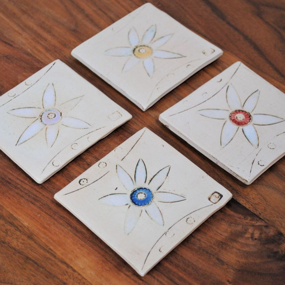 Set of four coasters with daisy design.