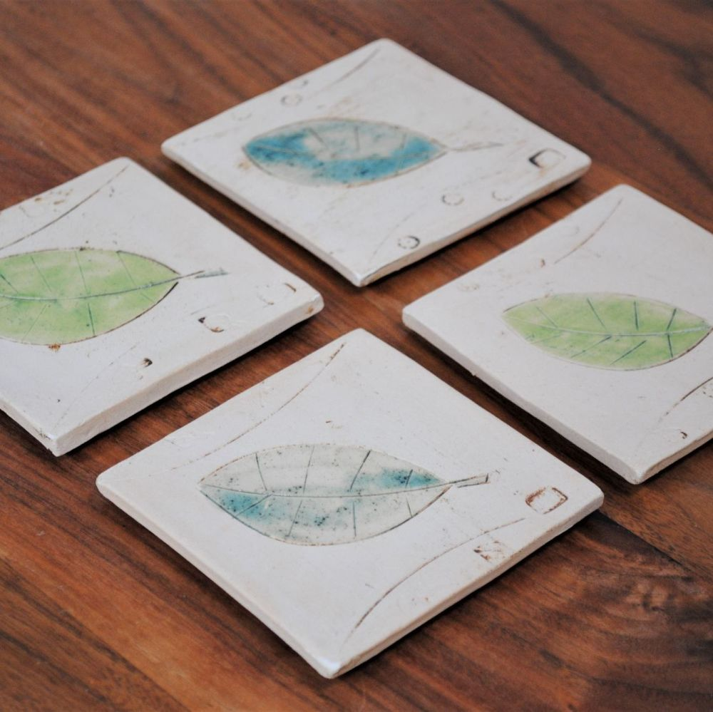 Set of four coasters with leaves design.