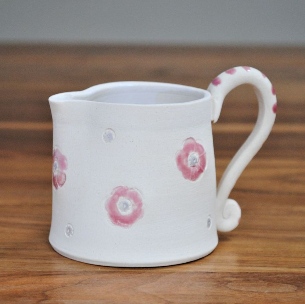 Jug thrown on the pottery wheel from white clay with pink details. Microwav