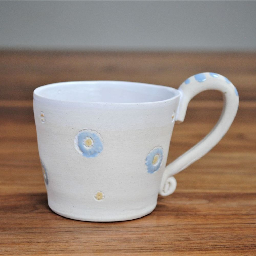 Mug thrown on the pottery wheel from white clay with blue and yellow detail