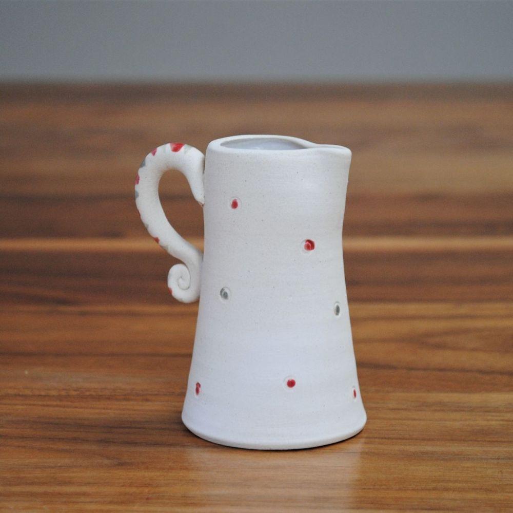 Mini jug thrown on pottery wheel from white stoneware with red & grey detai