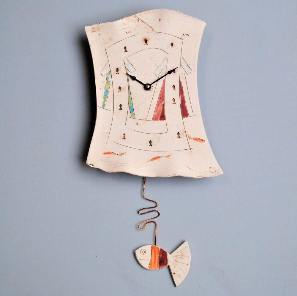 Handmade ceramic pendulum wall clock with beach huts and fish design.