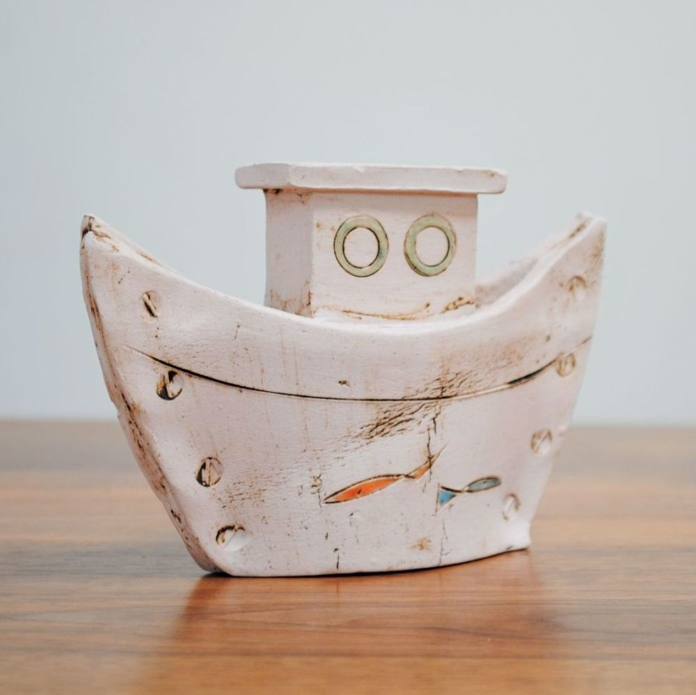 A small boat from white clay with fish design.