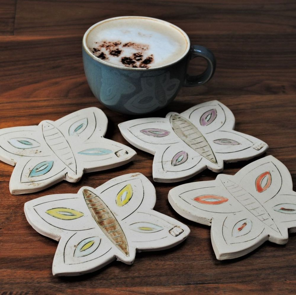 Butterfly shaped set of four ceramic coasters.