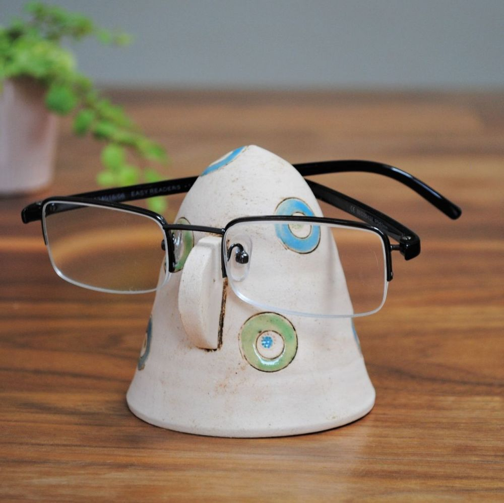 Handmade ceramic glasses stand from white clay, decorated with green and bl