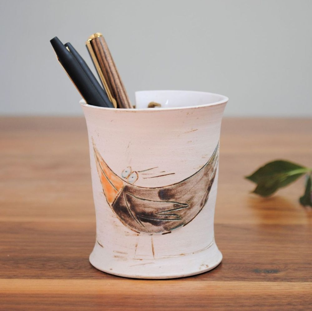 Handmade ceramic pencil holder from white clay decorated with bird.
