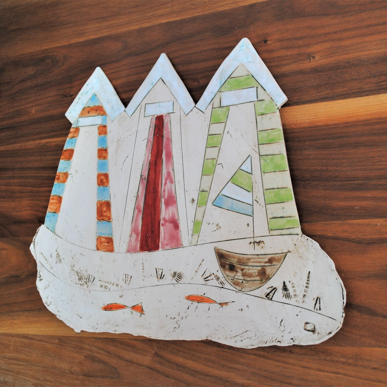 Wall art, ceramic hanging picture with beach houses, boat and fish.