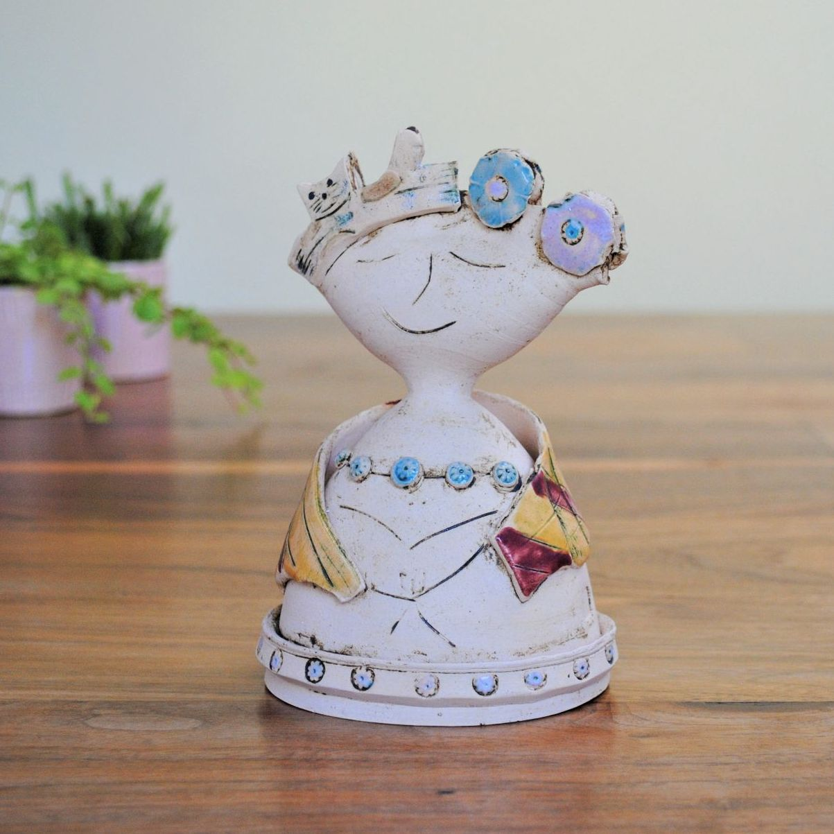 Ceramic sculpture lady with cat and flowers.
