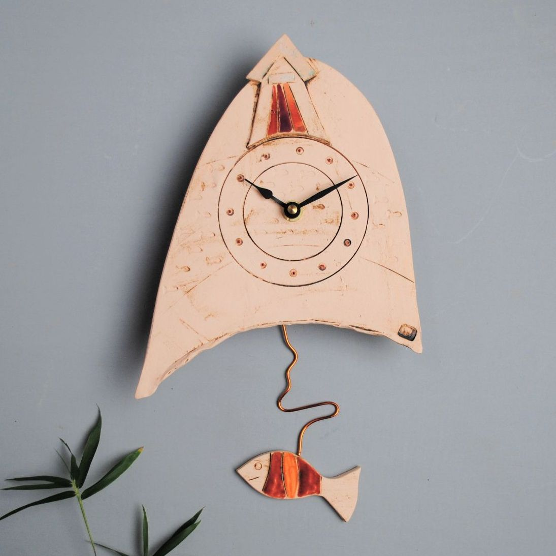Ceramic pendulum wall clock with beach hut and fish.