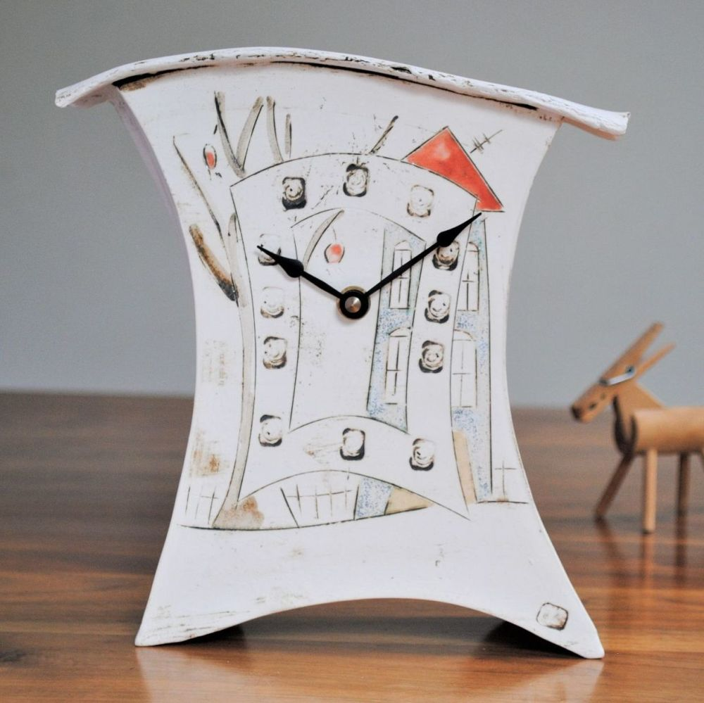 Ceramic mantel clock in a off white clay decorated with house and tree.