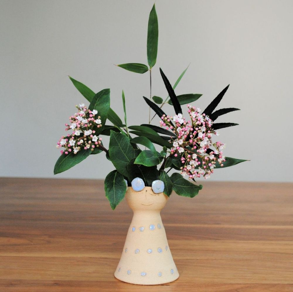 Vase with happy face and blue flowers.