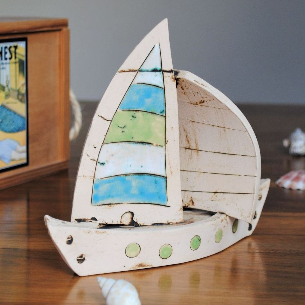 Large sailing boat made from white clay and decorated with white, red and b
