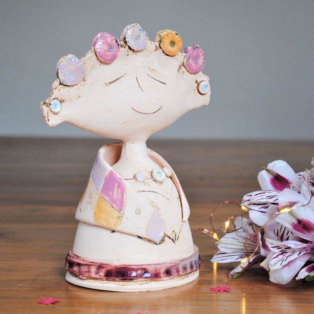 Lady sculpture with pink, purple and yellow flowers.